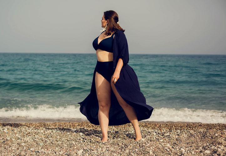 Woman walking on beach looking at water