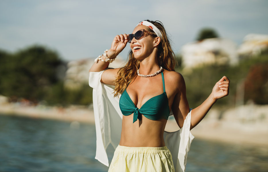 Woman smiling holding her sunglasses