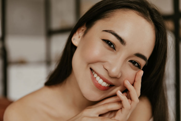 Woman smiling and touching her jaw